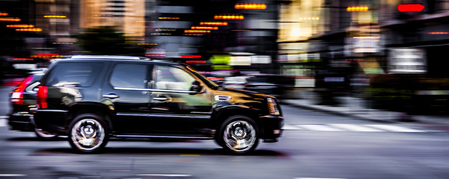 Black SUV speeding down a road in downtown Chicago