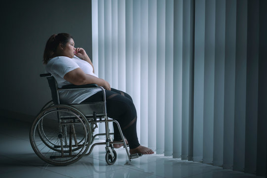 Disabled fat woman looks pensive near the window