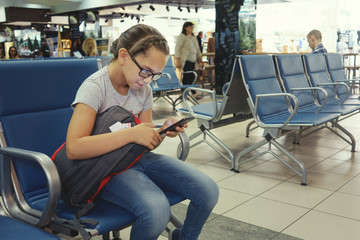 Cute girl in glasses is sitting at the airport in anticipation of the flight and looking into the smartphone.