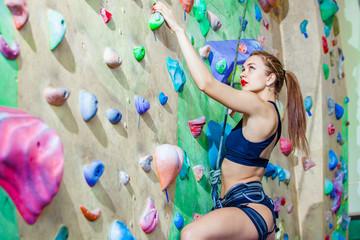 sexual woman climbing on a wall in an outdoor climbing center