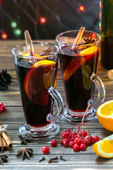 Christmas mulled red wine with spices and fruits on a wooden table. Traditional hot drink at New Year and Christmas time. Vertical Picture.