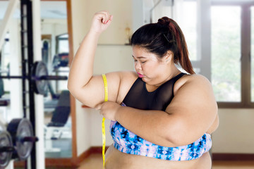 Young obese woman measuring her upper arm