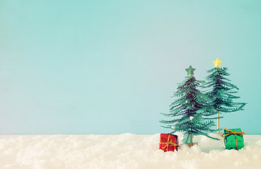 Image of paper christmas trees over white snow.
