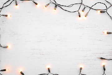 Wall Mural - Christmas lights bulb frame decoration on white wood. Merry Christmas and New Year holiday background. top view