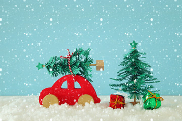 Red wooden car carrying a christmas tree over snow in front of blue background.