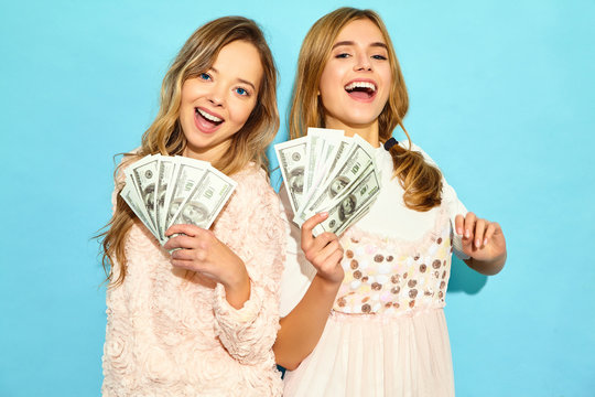 Portrait of two happy delighted blond girls wearing summer clothes rejoicing win and holding cash money isolated over blue background