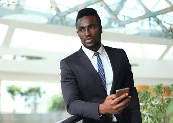 Successful African American businessman reading email on smart phone.