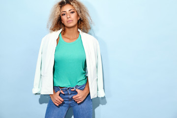 Portrait of beautiful smiling young black woman with blond african hairstyle. Model putting on her white jacket. Girl posing in casual modern clothes in studio on blue background