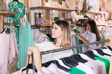 Woman customer looking green striped long sleeve shirt  in store