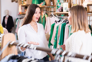 Two young women  friends talking  in  clothes shop and smiling