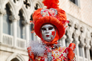 Colorful carnival orange-silver mask and costume at the traditional festival in Venice, Italy