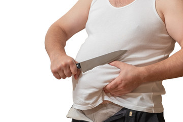 A man with one hand holds the fat fold on his big belly, and in the other hand holds a knife.