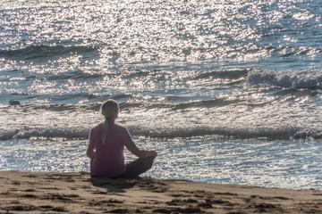 Woman Meditating on a Southern Italian Beach in the Sun