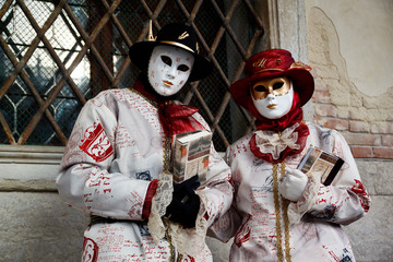 Colorful carnival red-white mask and costume at the traditional festival in Venice, Italy