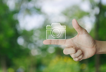 Camera flat icon on finger over blur green tree in park, Business camera service concept