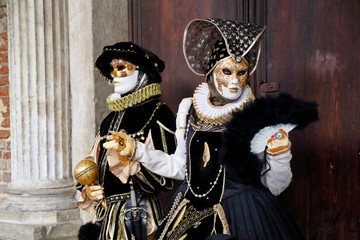 Colorful carnival black-white-gold mask and costume at the traditional festival in Venice, Italy