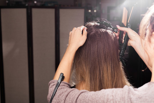 professional hairdresser clipping hair of a young model with a hairpin before making a beautiful coiffure in a beauty salon