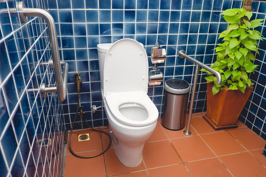 Public restroom for disabled and elderly people, handicap toilet with grab bars on the walls