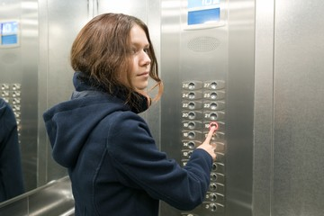 Young teen girl in the elevator, presses the elevator button