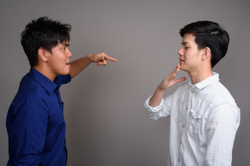 Two young handsome Asian men having argument