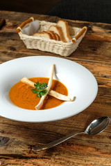 Vegetable pumpkin and carrot soup and basket with white bread