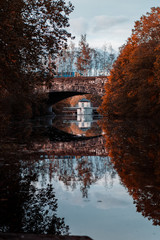 Canvas Prints Red Concrete arch bridge on a river with autumn tree color tones and sunset sunlight. Südsee in Braunschweig, Germany