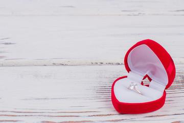 Diamond ring in heart-shaped gift box. Golden engagement ring in red velvet box on wooden background. Romantic gift for Valentines Day.