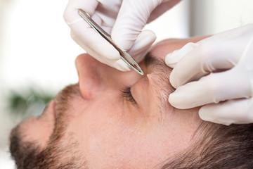 Fototapeta Kosmetyczka depiluje zbędne włosy na brwiach mężczyzny.
