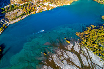 Beautiful turquoise color lake Issyk in mountainous area of Almaty region during colorful autumn with yellow birches and pine trees, Kazakhstan