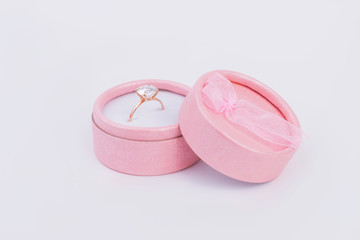 Golden ring with diamond in gift box. Pink gift box with engagement ring. Luxury gift for beloved woman.