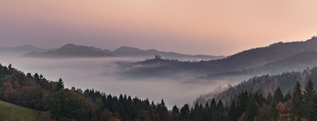 Panoramic foggy landscape at dawn over mountain and valley