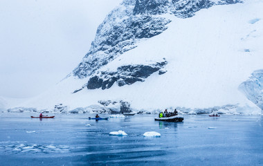 Spoed Foto op Canvas Antarctica Snowfall over the motor boat with tourists and kayaks in the bay with rock and glacier in the background, near Almirante Brown, Antarctic peninsula
