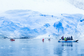 Snowfall over the motor boat with tourists and kayaks in the bay with huge blue glacier wall in the background, near Almirante Brown, Antarctic peninsula