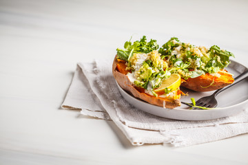 Quinoa Stuffed Sweet Potatoes with Kale and avocado, copy space, white background.