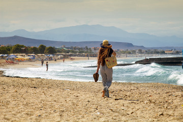 Beautiful teenager goes on the beach. The girl with her long hair is walking on the beach in Greece. A woman in a hat on the beach.