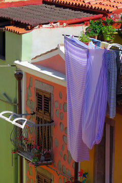 Blankets drying on a clothes line at a colourful house in the old village of Bosa, Sardinia, Italy