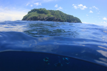 Scuba divers and island over under