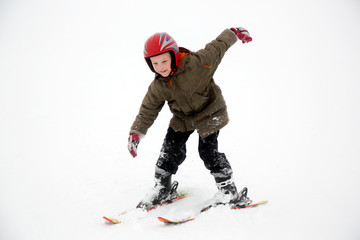 Young student boy practices ski sport moves. White snow background.