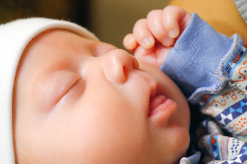 The baby sleeps sweetly with his mouth open. The child raised his hand to his face. Quietly dozing.