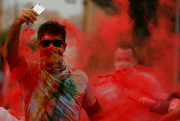 A participant films on his mobile phone as he gets covered in coloured powder during the 'Colour My Run' charity fun run on Manoel Island in Valletta's Marsamxett Harbour