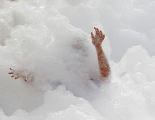 A participant runs through a foam bath during the 'Colour My Run' charity fun run on Manoel Island in Valletta's Marsamxett Harbour
