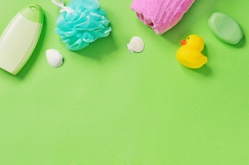 Flat lay photo baby cosmetics for skin and hair care. Organic shampoo, sponge, pink towel, soap and yellow rubber duck on a green background. Mockup, copy space