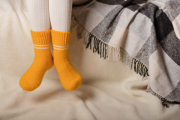Female legs in warm white knitted tights and yellow socks on a white background made of faux fur