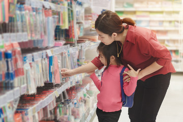 Back to school concept, Young asian mother or parent and little girl or pupil buying school supplies in store, Selective focus Wall mural