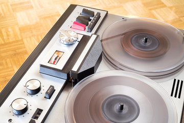 vintage reel to reel tape recorder in full operation, close up