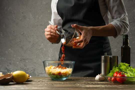 Freezing food is cooked in the process, shrimps are poured out by the chef of a vegetarian salad with seafood. The backdrop is a concrete wall with a text area
