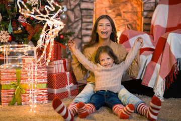Little girl child at home by the fireplace with the family parent mother and Christmas tree with gifts and luminous garlands celebrates Christmas