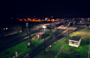 Freight yard at night with grass tracks and parked trains for maneuvering
