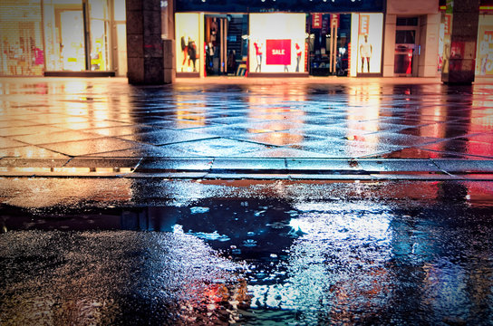German inner city with closed shops and sale with pedestrian zone in rain and night with red lights