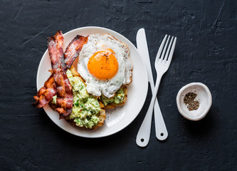 Healthy nutritious breakfast - avocado toast, bacon and fried egg on dark background, top view